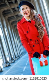 Bright in Paris. smiling trendy tourist woman in red trench coat on Pont de Bir-Hakeim bridge in Paris with shopping bag and Christmas present box