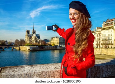 Bright in Paris. smiling young traveller woman in red trench coat on embankment in Paris, France with smartphone taking photo