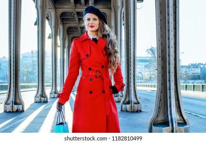 Bright in Paris. young traveller woman in red trench coat on Pont de Bir-Hakeim bridge in Paris with shopping bag