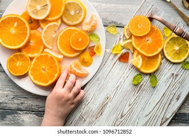 Bright photo of different citrus fruits over wooden background and child's hand draging a tangerine