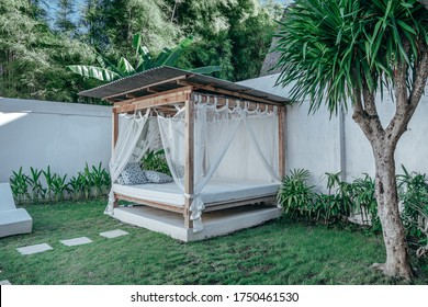 Bright photo of a gazebo with a wooden bed under a mosquito grid on a outside