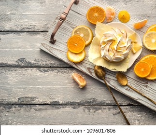 Bright photo of lemon tart and different citrus fruits over wooden background
