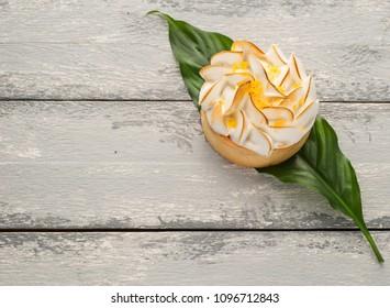 Bright photo of lemon tart on the leaf over wooden background