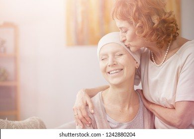 Bright photo of senior redhead woman kissing forehead of her happy cancer sick sister
