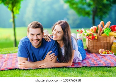Bright photo of young happy smiling couple in love, lying together on a picnic blanket, outdoors