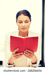 bright picture of calm and serious woman with book