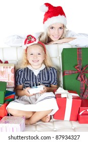 Bright picture of happy mother and little girl dressing in Santa's Helper hat with gifts over white