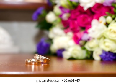 Bright picture with wedding rings and colorful wedding bouquet on the table
