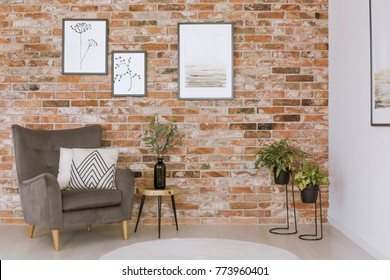 Bright pillow on grey armchair and plants in living room with gallery of paintings on red brick wall
