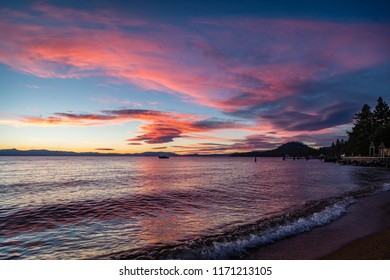 Bright pink and blue sunset with gentle waves in lower right corner from Lakeside Beach at Lake Tahoe