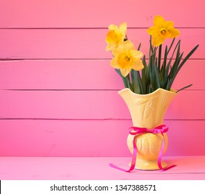 Bright Pink Boards Background with Yellow Daffodils in Vintage Vase with space for copy, text or words.