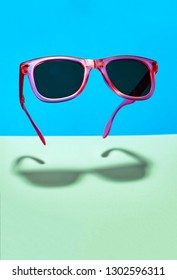 Bright pink colour sun glasses in the air. Floating in the air pink sunglasses on pastel tones blue and green background.  Lower shadow below the glasses. Minimalism summer concept.