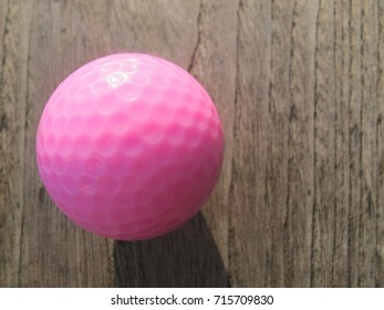 bright pink golf ball lies on a wooden surface lit by the light of the evening sun