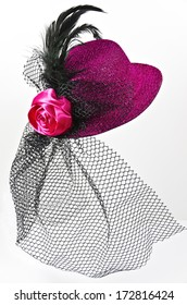 Bright pink  lady's hat with a black veil isolated on white - a carnival costume accessory