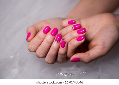Bright pink manicure with sparkling crystals on the ring fingers on the white background