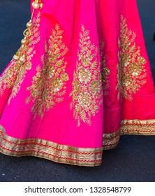 Bright pink silk sari or saree decorated with gold designs.