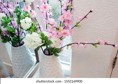 Bright pink and white colored fake flowers in a white vase near a window on a light day, plastic flowers in modern room beauty