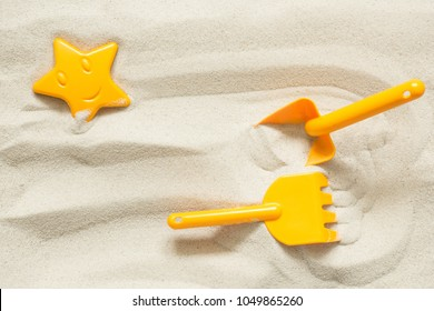 Bright plastic children's toys in the sand. Concept of beach recreation for children. Top view. Space for text.