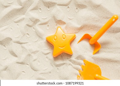 Bright plastic children's toys in the sand. Concept of beach recreation for children. Children's summer games. Summer concept. Flat lay, top view, copy space
