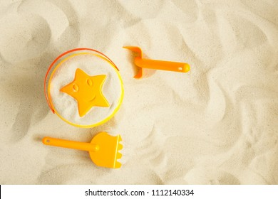 Bright plastic children's toys in the sand. Concept of beach recreation for children. Top view. Space for text. Flat lay, top view, copy space