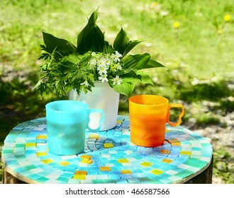 bright plastic cups and simple flowers on a simple rough table in the garden. Sunny spring summer day.