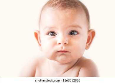 bright portrait of adorable baby on airy beaige background isolated with big eyes and ears and cheecks childhood