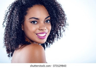 Bright portrait of beautiful young mixed race woman with curly hair on white background. Girl looking at camera and smiling