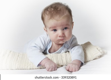 Bright portrait of blue-eyed adorable child lying on his tummy