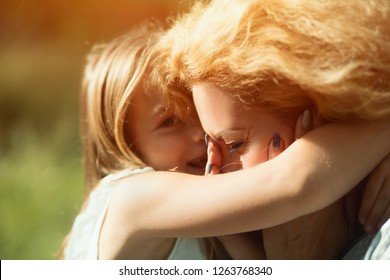 Bright Portrait. Cute Blonde Girl Hugs Tight Her Mother Who Is Crying From Happiness. Portrait Of Disabled Woman Crying When Being Hugged By Daughter
