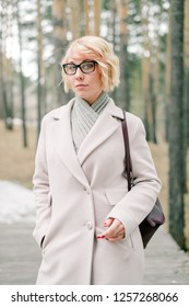 Bright portrait of a girl in a white coat and big glasses