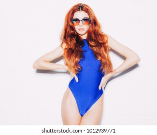 Bright portrait of an incredible beautiful long-haired redhead sexy girl in blue swimsuit with trendy sunglasses posing against a white wall showing an incredible attractive body. Indoor.