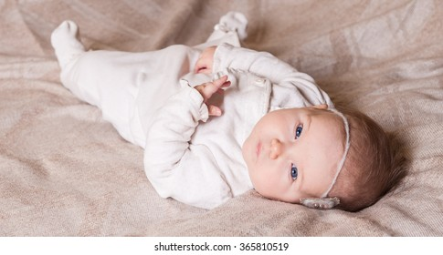 Bright portrait of a sweet little 5 months old baby girl looking up