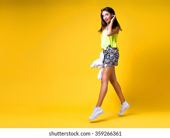 Bright positive fashion studio portrait of pretty young hipster girl, bright make up, sexy body, stylish trendy neon outfit, smart casual, cute emotions, color pop, yellow background. Spring time.