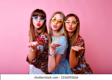Bright positive portrait of three happy hipster woman having fun and sending air kisses to camera, color matching summer clothes and colorful sunglasses, pink background, youth girls party.
