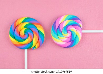 A bright primary colored lollipop and pastel colored lollipop in perpendicular positions on pink.