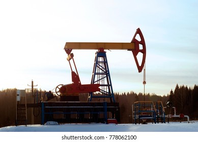 a bright pumpjack over an oil well in a winter snowy forest landscape