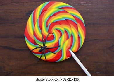 Bright rainbow lollipop candy with black spider on dark wood table for Halloween Trick or Treat.