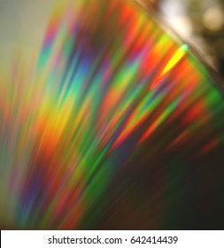 Bright rainbow reflection on CD with blurred background.