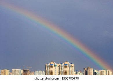 Bright rainbow in the sky above urban houses after a thunderstorm.