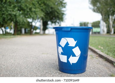 Bright recycle bin with label on the road without people. Concept of envirometal protection. Cleaned outside terrain.