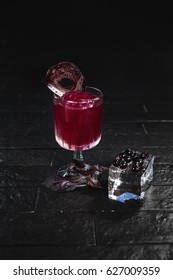 Bright red alcohol cocktail with beet garnish with basil and blackberries on ice cube on black background