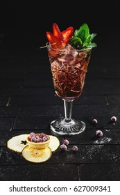 Bright red alcohol cocktail with strawberry garnish with ice, berries and mint on black background