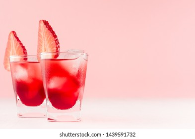 Bright red alcoholic shots in two shot glasses with strawberry slice, ice cubes in trendy modern bar interior in pastel pink color on white wood board.