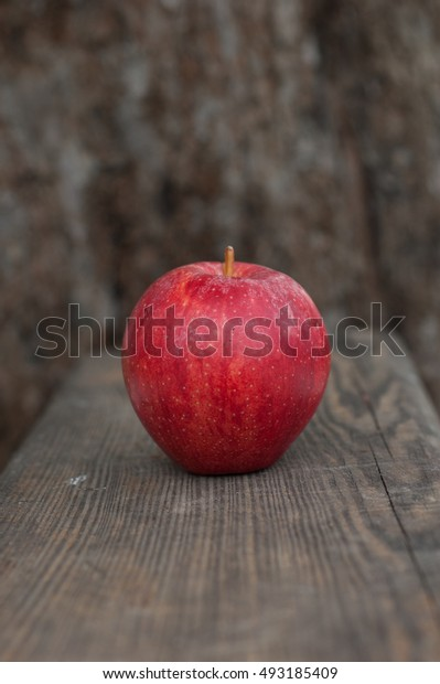 Bright red apple on a wooden background.