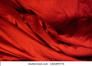 Bright red background of fabric lined with natural waves. Crumpled bedding, sexy folds. The texture of the fabric.