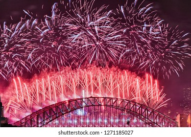 Bright red balls over the top of Sydney Harbour bridge arch against black dark sky during new year midnight fireworks celebrating annual event.