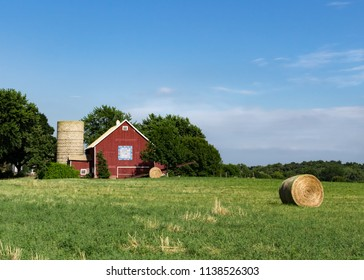 Bright red barn with barn quilt, a silo & round hay bales. Colorful small family farm surrounded by green fields and trees. Concepts of farming, agriculture, Americana, agribusiness, agritourism