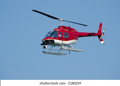 A bright red Bell 206 Jet Ranger helicopter with a camera on a Fleet Week Air Show in 2006. A little motion blur on rotor blades