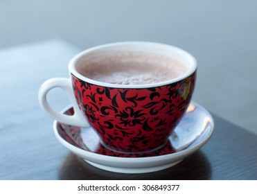 A bright red and black cup of cocoa on a wooden table surface