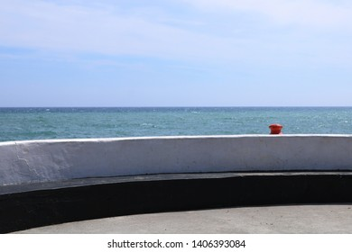 A bright red bollard is visible along a sea wall. The wall is white the sea is blue. Typical coastal image could be used in coastal holiday homes.